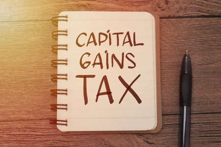 Capital Gains Tax, text words typography written on book against wooden background, life and business motivational inspirational concept Banque d'images