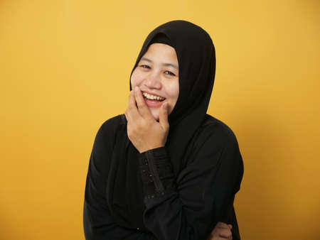 Portrait of muslim lady wearing hijab laughing to see somwthing funny, happy cheerful expression, against yellow background Foto de archivo