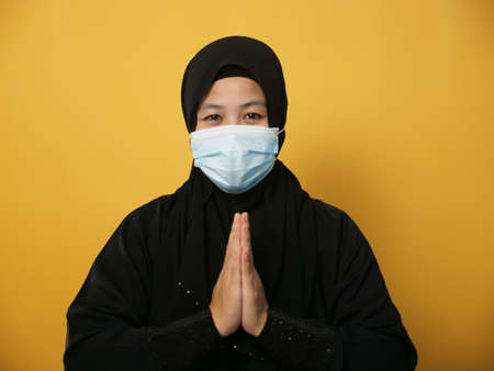 Asian muslim woman wearing hijab and mask during pandemic new normal, woman wearing face protective mask doing greeting gesture, against yellow background Archivio Fotografico