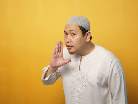 Portrait of young Asian muslim man asking to be quiet, shushing gesture, silence concept, against yellow background