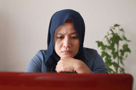 Asian muslim woman wearing hijab looking at her laptop seriously, work from home concept. Young successful female businesswoman or entrepreneur working at home Banco de Imagens
