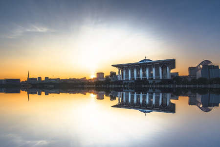Sunrise scenery of Putrajaya Public Mosque with reflection. 免版税图像