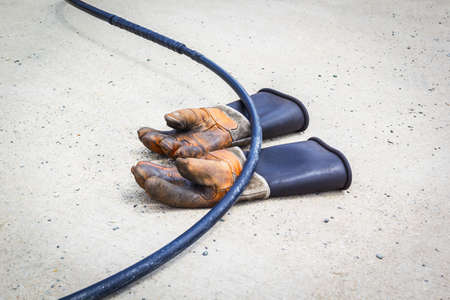 Old Dirty Leather Work Gloves and electric cable. photo