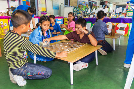 intensely: MUEANG, CHIANG MAI, THAILAND-FEBRUARY 09 : Kids playing chess laying on the floor and thinking intensely in Academic Day 2015 Kowitthamrong School Mueang, Chiang Mai, Thailand on FEBRUARY 09, 2015