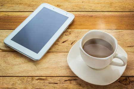Hot coffee and tablet on wood table photo