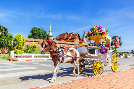 cartage: Horse carriage Parking in front of Wat Phrathat Lampang Luang temple for services to tourists in Lampang, Thailand Stock Photo