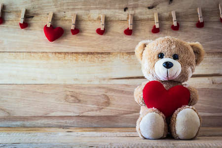 Teddy bear holding a heart-shaped pillow Archivio Fotografico