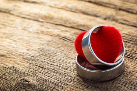 proposal of marriage: Close up shot Two ring and heart shape on plank wood board, valentine concept