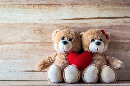 Couple teddy bear with Pink heart-shaped pillow on plank wood board, Valentine concept Zdjęcie Seryjne