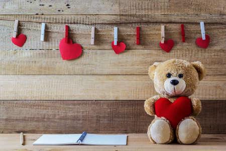 juguetes de madera: Una foto del oso de peluche que sostiene una almohadilla en forma de corazón en la mesa de madera con papel de la libreta Foto de archivo