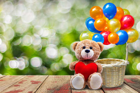 A photo o Teddy bear holding a heart-shaped pillow With green bokeh background Stock Photo