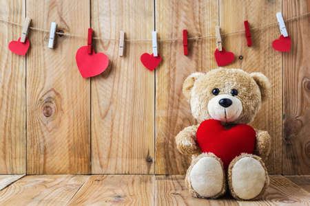 heartshaped: A photo of Teddy bear holding a heart-shaped pillow on plank wood board with wood board background
