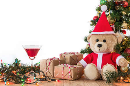 A photo of Teddy Bear in Santa Cross Dress Sitting up against the christmas tree with gift box and red wine on white background
