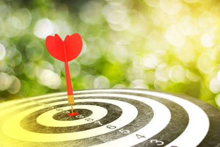 Red arrow on target dart over blurred bokeh background, metaphor to target marketing or target arrow concept, Selective focus Stock Photo