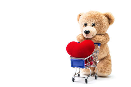 A photo of teddy bear with heart shaped pillow in a cart on isolate white background with space for copy text