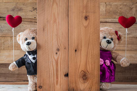 A photo of cute teddy bear holding heart-shaped balloon with wood board texture