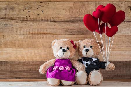 A photo of teddy bears holding heart-shaped balloon with wood board texture Zdjęcie Seryjne