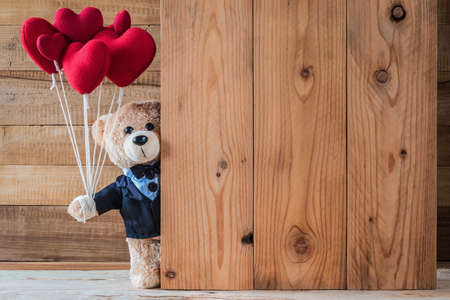 A photo of teddy bear holding heart-shaped balloon with wood board texture