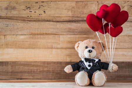 A photo of teddy bear holding heart-shaped balloon sitting on wood board