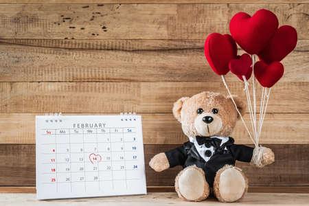 A photo of teddy bear holding heart-shaped balloon sitting near calendar in valentine day on wood board