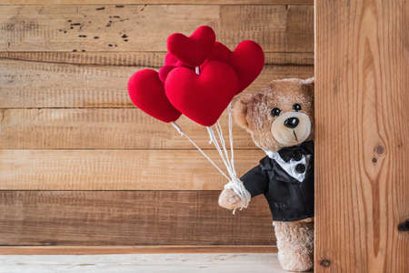 Une photo de mignon nounours tenant un ballon en forme de coeur avec texture de planche de bois Banque d'images - 91176320