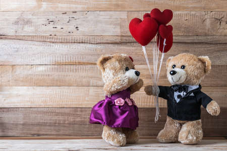 A photo of teddy bear give heart-shaped balloon to his girl friend