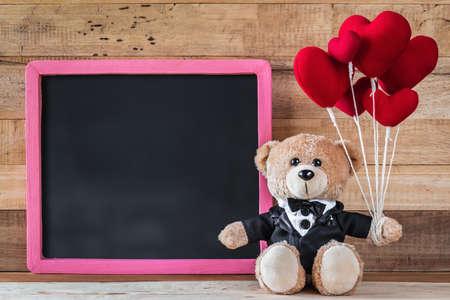 A photo of Cute teddy bear holding heart-shaped balloon with Blackboard on wood board texture