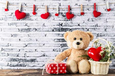 A photo of teddy bear sitting near red gift box with white brick wall background, Valentine concept Zdjęcie Seryjne