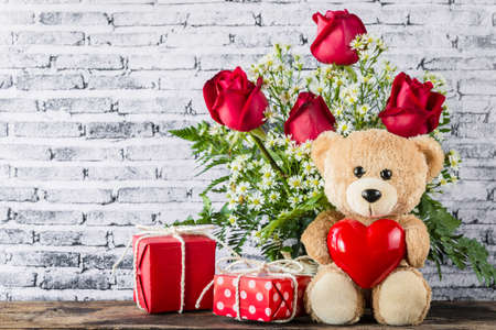 A photo of Teddy bear holding a heart-shaped balloon with red gift box and white brick wall background, Valentine concept
