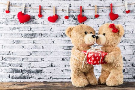 A photo of Teddy bear have a gift to girl friend with white brick wall background, Valentine concept