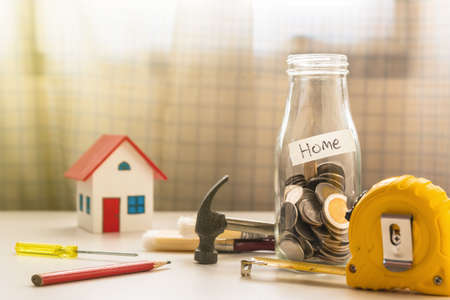 A photo of coin in glass bottle with capenter tool, Saving for new home concept