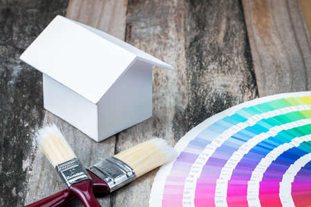 A photo of small white house model with color bar and brush, This photo shoot in concept Home painting color design