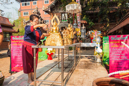 CHIANGMAI, THAILAND-APRIL 14 : Songkran Festival is celebrated in a traditional New Years Day, Unidentified old woman sprinkle water onto a Buddha Statue in Wat Loke Moli. on April 14, 2018 in Chiang Mai,Thailand. Publikacyjne