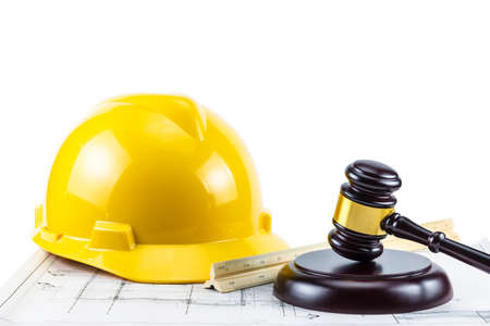 A photo of gavel and yellow safety helmet on isolate white background. Concept idea Law about construction design Zdjęcie Seryjne