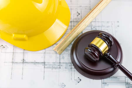 A photo of gavel and yellow safety helmet. This photo shot in concept idea Law about construction design