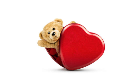 A photo of teddy bear pop out of red box heart shape on white background.