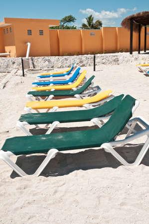 メキシコ観光客を待っている空のビーチチェア、背景がオレンジでペイントした建物