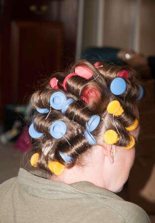 彼女の髪の色のローラーと若い女性