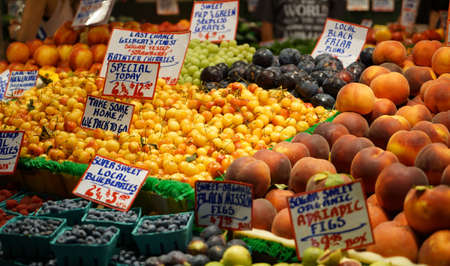 Outdoor fruit market with signs and pricing