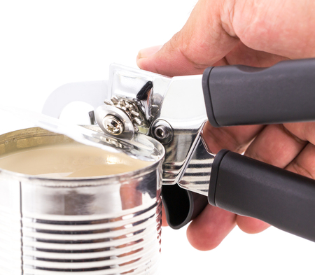 cooking implement: Tin opener opening a can on white background Stock Photo