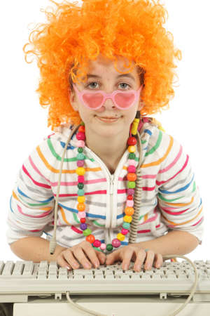 Young girl working and writing on a computer and disguised with fun glasses and orange style hair, isolated on white background