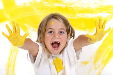 little girl painting with his yellow hands on white paper background