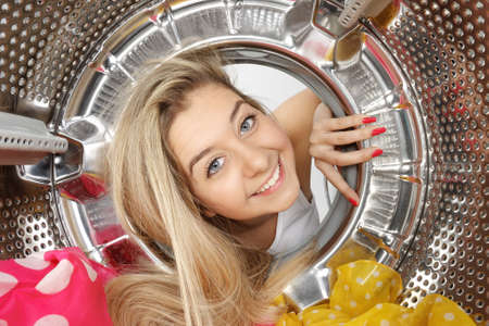 Portrait of a young blonde woman looking inside view of a washing machine drum