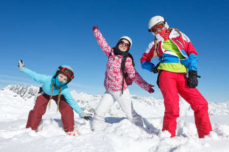 Long live family ski holidays and mountain vacations. A group of children on winter sport vacation playing in the snow on the ski slopes in the Alps, France Banque d'images