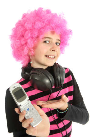 Young girl with pink hair and headphones shows her cell phone, isolated on white background