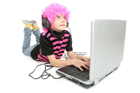 Young girl writes on a laptop listening music, isolated on white background Banque d'images