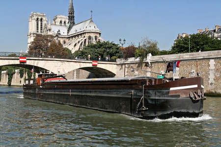 Notre Dame of Paris seen from the quai de Seine with boat. The famous and historic place of paris.