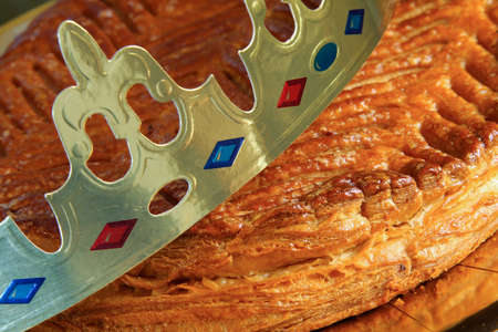 Traditional galette des rois or French king's cake with golden paper crown placed on it 版權商用圖片