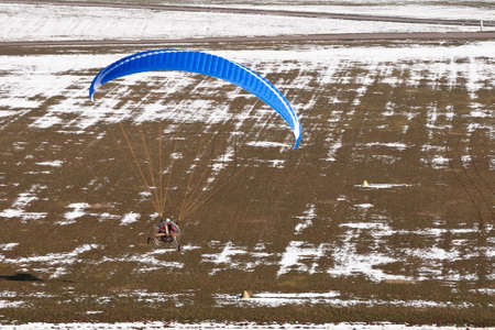 Extreme sports pilot flying with a paramotor engine and a paraglider prepares to land on the ulm runway Banque d'images