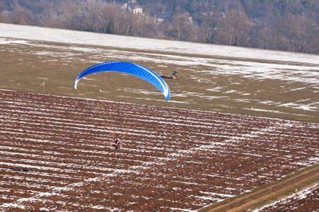 Motorized paraglider or paramotor preparing to land on a light aircraft runway for ULM in winter under the snow